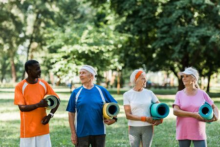 happy senior and multicultural pensioners holding fitness mats while standing in park Foto de archivo - 130218801