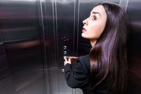 scared businesswoman, suffering from claustrophobia, looking up while pushing button in elevator
