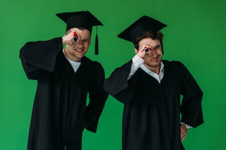 two happy students in academic caps holding diplomas isolated on green