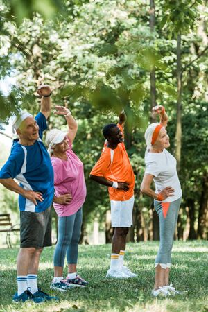 selective focus of cheerful multicultural senior men and women standing with hands on hips while doing exercise