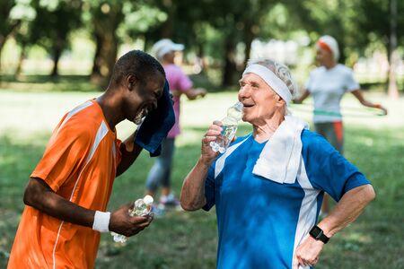 selective focus of sportive multicultural retired men holding bottles with water near senior women Foto de archivo - 130219521
