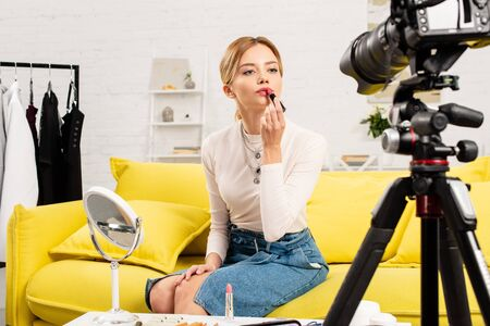 beauty blogger applying lipstick in front of video camera