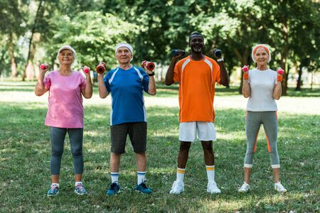 cheerful multicultural pensioners in sportswear exercising with dumbbells in park Foto de archivo - 130219995