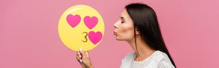 panoramic shot of woman holding kissing smiley isolated on pink