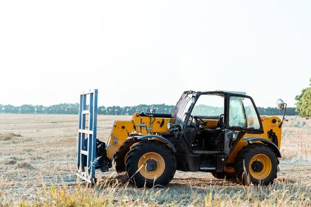 modern tractor on wheat field in country