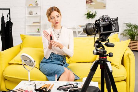 beauty blogger holding lipstick in front of video camera