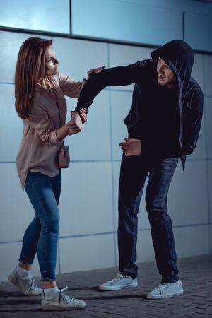 jolie femme se battre avec un voleur dans le passage souterrain