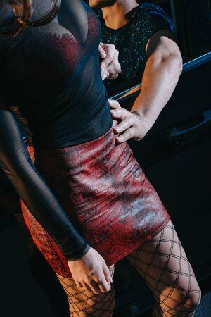 vista ritagliata del cliente che tocca seducente in gonna rossa in piedi vicino all'auto Archivio Fotografico