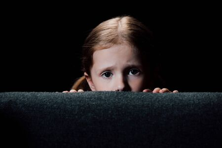 scared child hiding behind armchair and looking at camera isolated on black Imagens