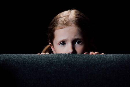 verängstigtes Kind, das sich hinter einem Sessel versteckt und isoliert auf schwarz in die Kamera schaut Standard-Bild