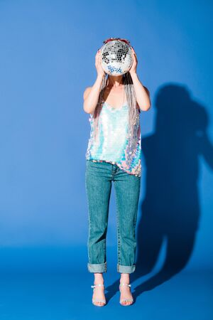 stylish girl covering face with disco ball on blue