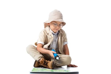 explorer child in hat and glasses holding flashlight and looking at map on white