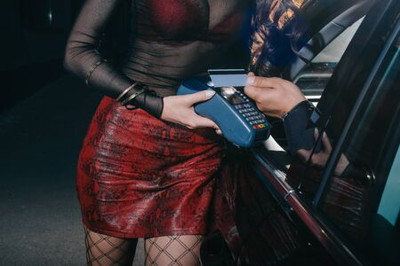 cropped view of man paying by credit card while prostitute holding credit card reader