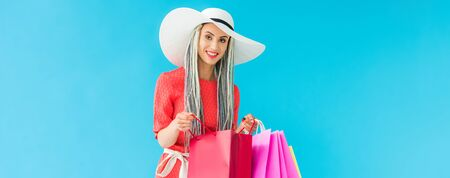 panoramic shot of beautiful stylish girl with shopping bags isolated on turquoise