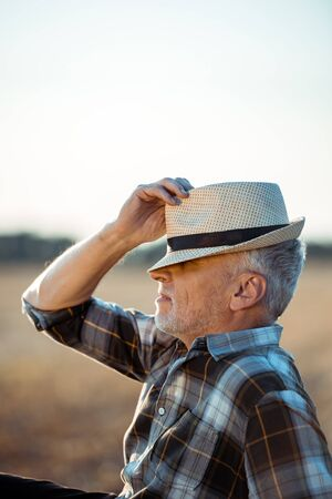 self-employed farmer with closed eyes touching straw hat