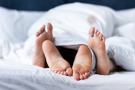 partial view of two barefoot lesbians lying under blanket Stock Photo