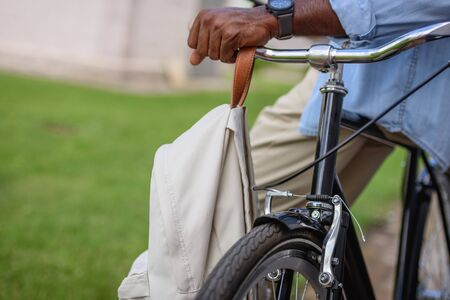 cropped view of african american man standing near bicycle with backpack Stockfoto