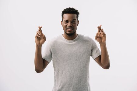 stressed african american man standing with fingers crossed isolated on white
