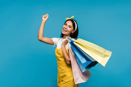 happy young woman holding colorful shopping bags and gesturing isolated on blue Stock Photo