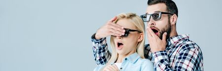 panoramic shot of shocked man Covering Eyes of girl in 3d glasses while watching movie isolated on grey