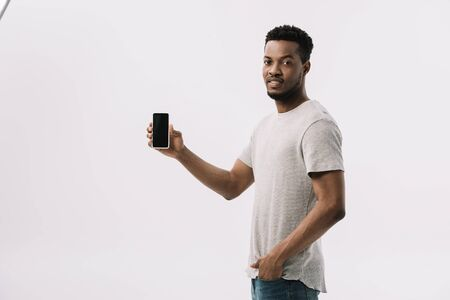 handsome african american man standing with hand in pocket and holding smartphone with blank screen on white Stock Photo