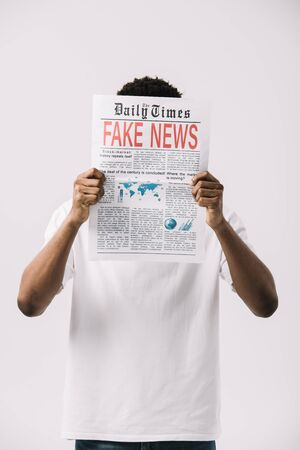 african american man covering face while reading newspaper with fake news lettering isolated on white