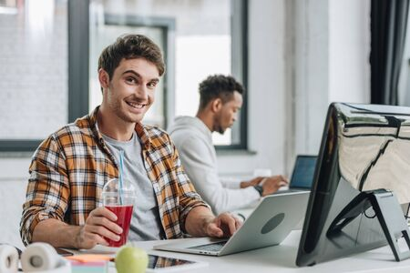 cheerful programmer looking at camera while sitting near african american colleague