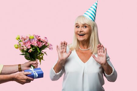 cropped view of senior man giving presents to happy wife in party cap isolated on pink