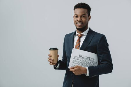 cheerful african american man holding business newspaper and paper cup isolated on grey