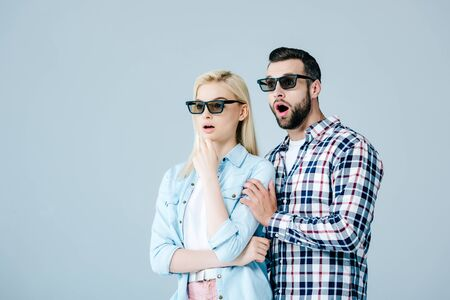 shocked man and girl in 3d glasses watching movie isolated on grey
