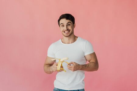 front view of excited muscular man in white t-shirt holding banana isolated on pink Imagens