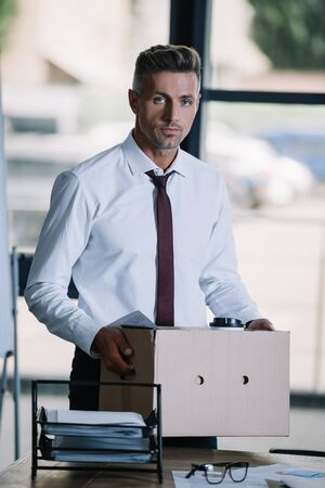 dismissed businessman holding box while standing near workplace and looking at camera Stock Photo