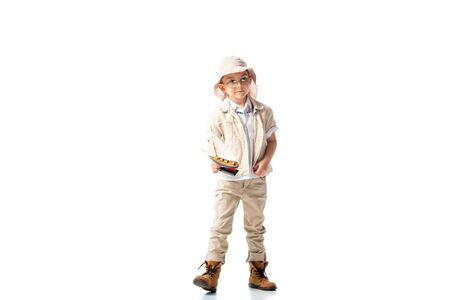 full length view of explorer child in glasses and hat holding toy ship on white Banco de Imagens - 130111386
