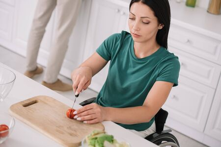 young disabled woman cutting tomato on chopping board while preparing salad in kitchen