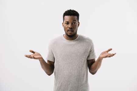 confused african american man showing shrug gesture isolated on grey