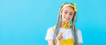 panoramic shot of happy girl with dreadlocks holding lollipop isolated on turquoise
