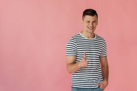 smiling man in striped t-shirt standing with hand in pocket, blinking and showing thumb up isolated on pink Stock fotó