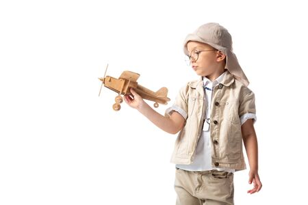 dreamy explorer boy in glasses and hat holding wooden toy plane isolated on white