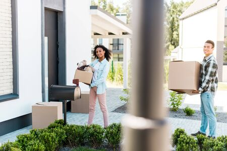selective focus of african american couple walking to house, holding boxes and looking at camera Imagens