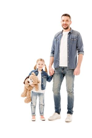 full length view of smiling dad and daughter in jeans holding hands isolated on white Imagens