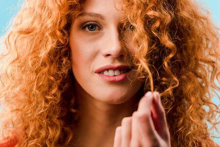 Retrato de mujer sonriente sosteniendo el pelo rizado rojo aislado en azul
