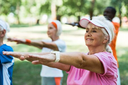 selective focus of retired woman doing exercise near multicultural pensioners in park Stockfoto