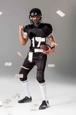 excited American Football player with ball on grey with falling money