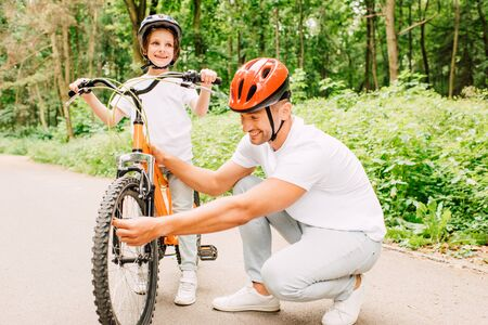 father in helmet checking wheel of bicycle while son standing in helmet and looking away