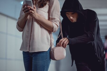 thief stealing money from bag of woman using smartphone