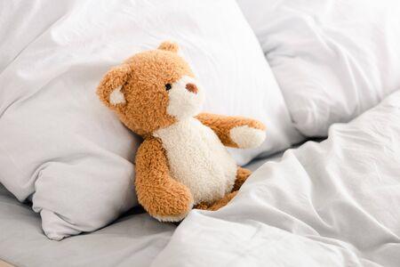 Oso de peluche en la cama con manta y almohadas blancas
