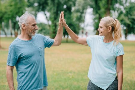 mature, cheerful sportsman and sportswoman giving high five and looking at each other Stockfoto