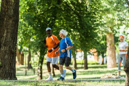 Selektiver Fokus glücklicher multikultureller Männer, die mit einer Frau im Ruhestand laufen