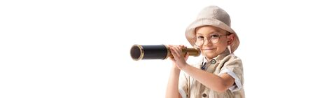 panoramic shot of smiling explorer boy in hat and glasses holding spyglass isolated on white Banco de Imagens - 130118130