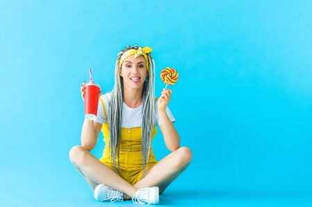 girl with dreadlocks and soda drink sticking out tongue and holding lollipop on turquoise